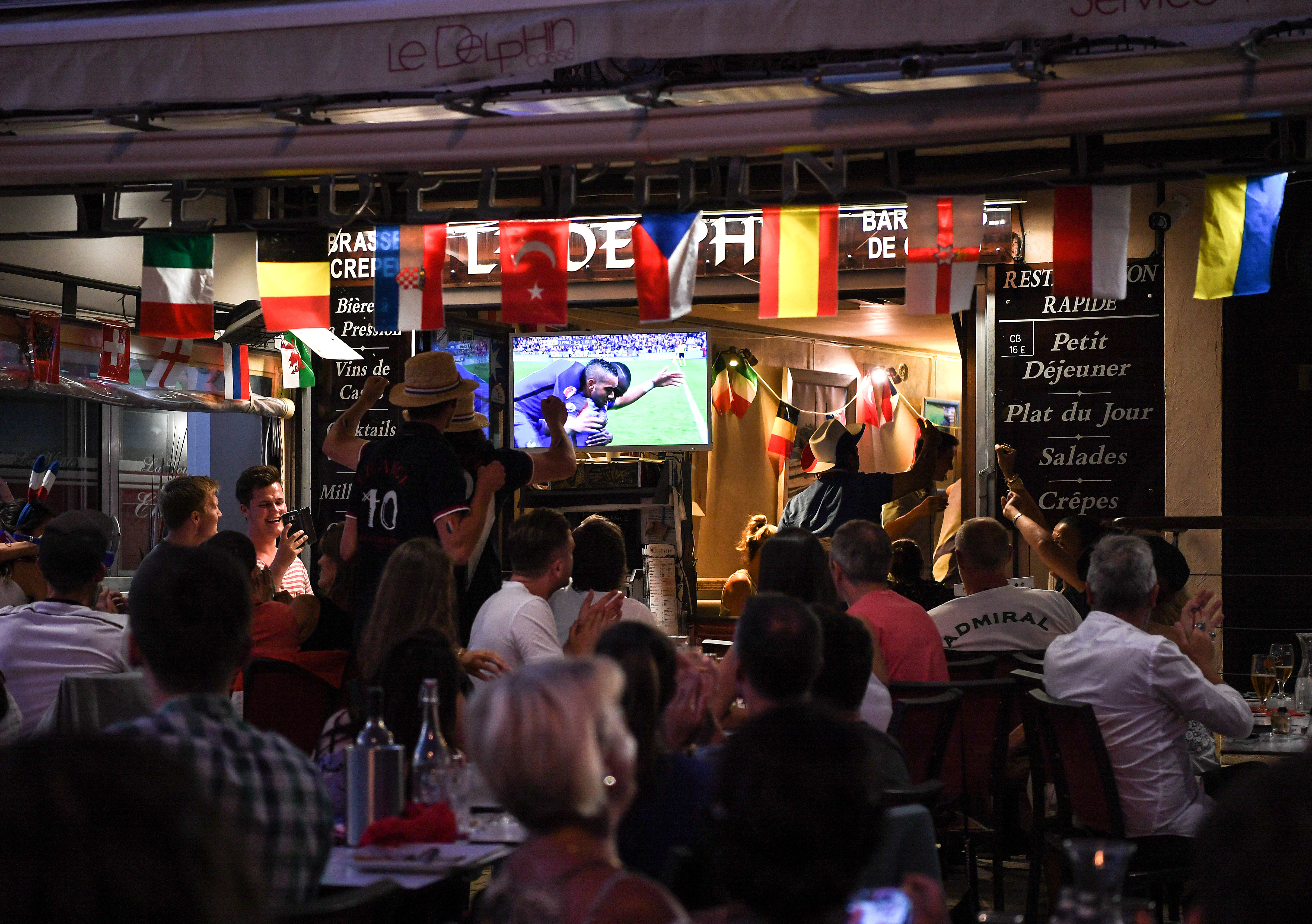 Visitors of a restaurant watch the Euro 2016 Quarter final between France and Iceland in Cassis, France, 03 July 2016. Photo: Federico Gambarini/dpa +++(c) dpa - Bildfunk+++ | Verwendung weltweit
