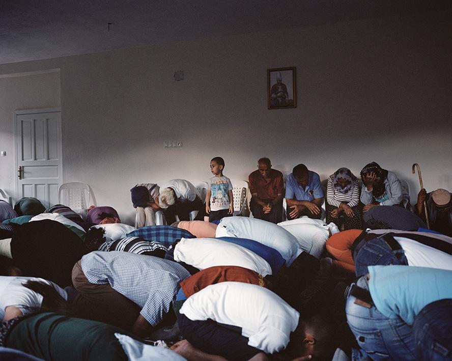 Ein Junge in einem Cem Evi (Versammlungshaus). Cem Evis werden von den Aleviten anstelle von Moscheen genutzt. Im Gegensatz zum Islam beten und singen Frauen und Männer gemeinsam