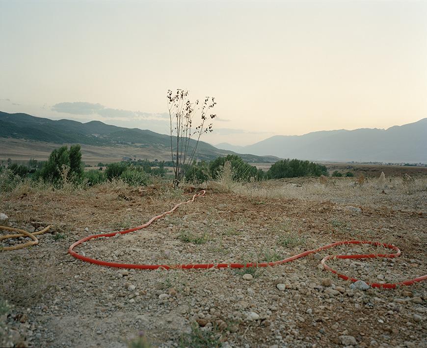 Ein Wasserschlauch schlängelt sich über den Boden eines Friedhofs Nahe Ovacık.