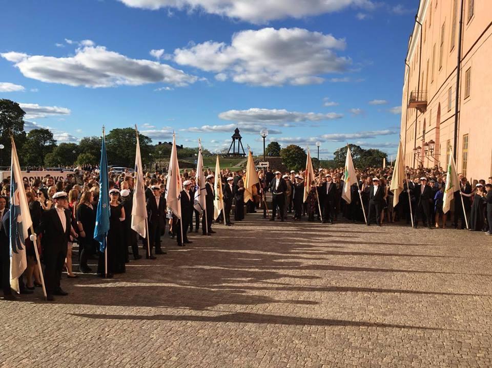 """""""Recentiorsmottagning"""" ist die offizielle Begrüßung der neuen Studierenden in Uppsala vor dem Schloss. Zu sehen sind die Fahnen der verschiedenen Nationen und auch die typischen, weißen schwedischen Studentenmützen."""