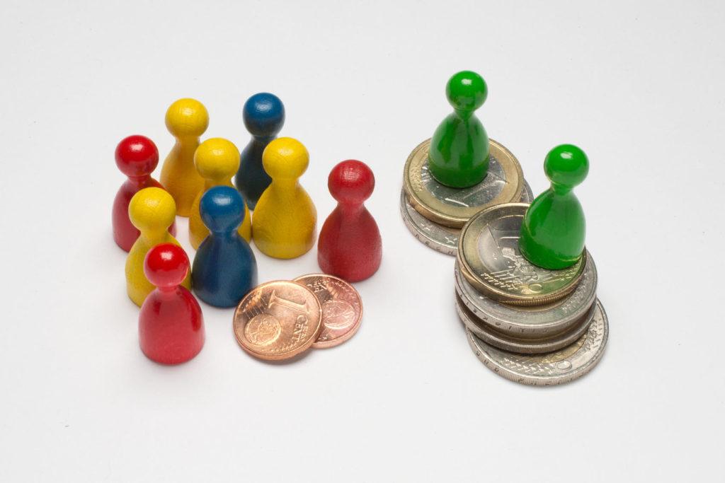 Spielfiguren mit Euro und Cent Münzen. Zwei Spielfiguren stehen auf 1 und 2 Euro-Münzen, neun weitere versammeln sich um zwei 1 Cent-Münzen, aufgenommen am 27.08.2015 im F.A.Z.-Studio in Frankfurt.
