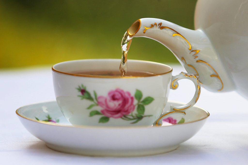 Tee wird in eine Tasse gegossen
