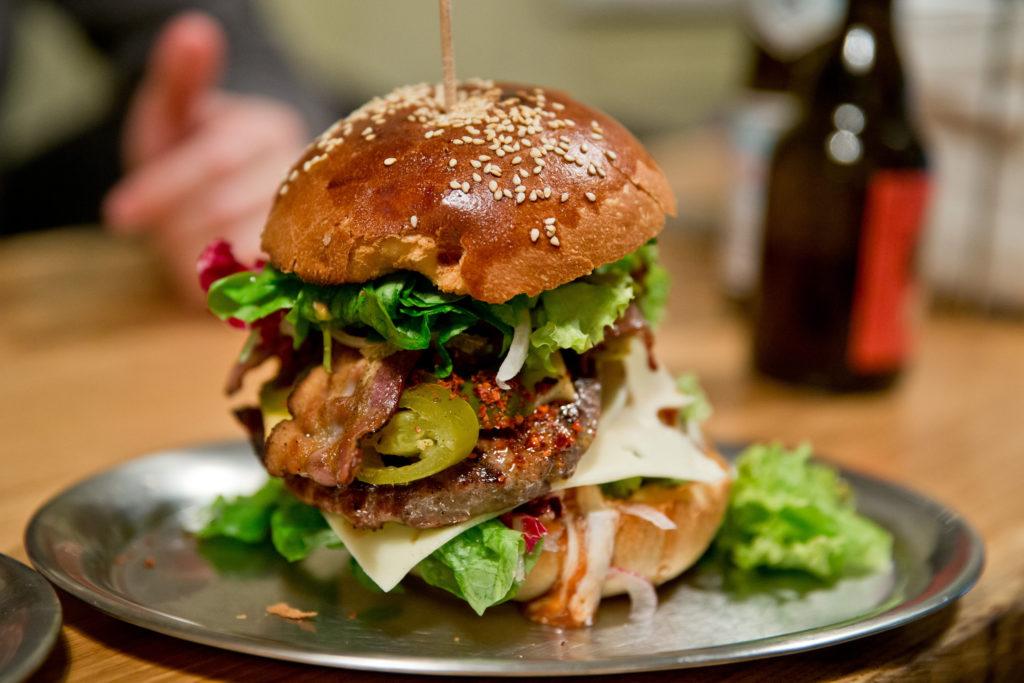 ARCHIV - ILLUSTRATION - Ein Burger mit Hackfleisch, Zwiebeln, Käse, Salat, Speck und Sauce, aufgenommen am 09.03.2015 in einem Burger-Restaurant. Foto: Daniel Karmann/dpa (zu dpa «Restaurants in New York müssen vor zu salzigen Speisen warnen» vom 01.12.2015) +++(c) dpa - Bildfunk+++