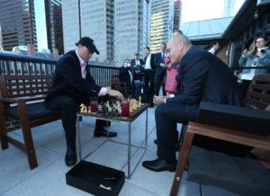 Filmstar Woody Harrelson (links) mit Andrei Filatow, Präsident des Russischen Schachverbands, beim Cocktailschach auf der Terrasse (Foto: Rob Kim/Getty Images für Agon Limited)