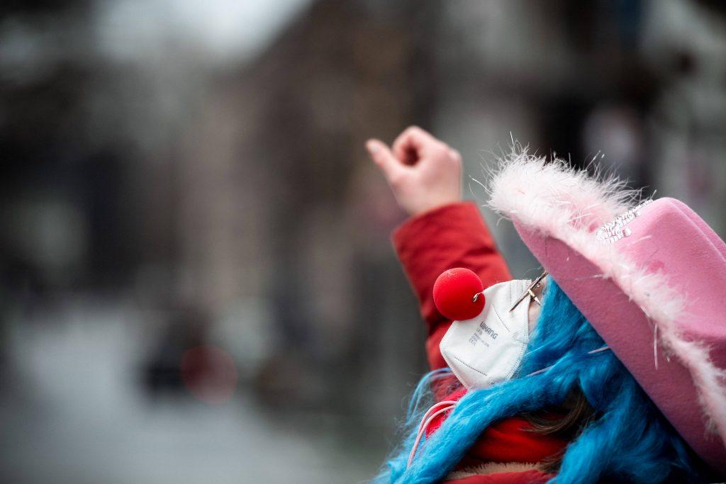 Die Straßen sind leer, die Clownsnase muss auf der Maske halten: Straßenkarneval an Rosenmontag in Düsseldorf.